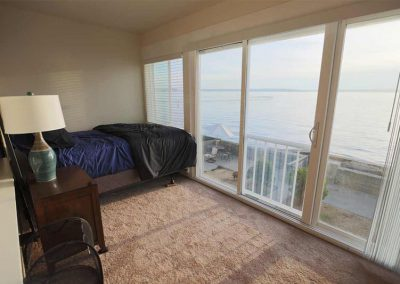 Photo of bedroom with large windows with view of back yard and water