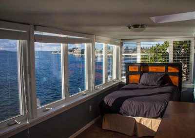 Photo of bedroom with large windows and water view in the West Seattle Men's Sober Living Facility