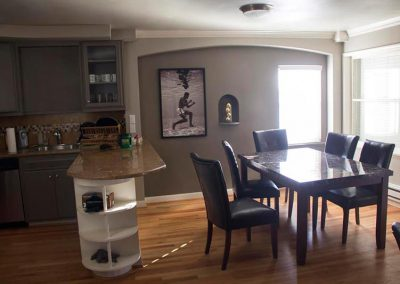 Photo of dining table with chairs and partial view of the kitchen in the West Seattle Men's Sober Living Facility