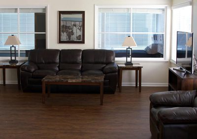 Photo of Living Room with couch, chair and TV in the West Seattle Men's Sober Living Facility