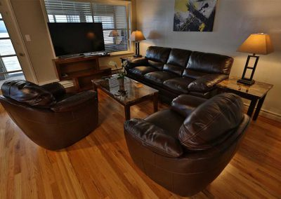 Photo of Living Room with comfy couch and chairs in the West Seattle Men's Sober Living Facility